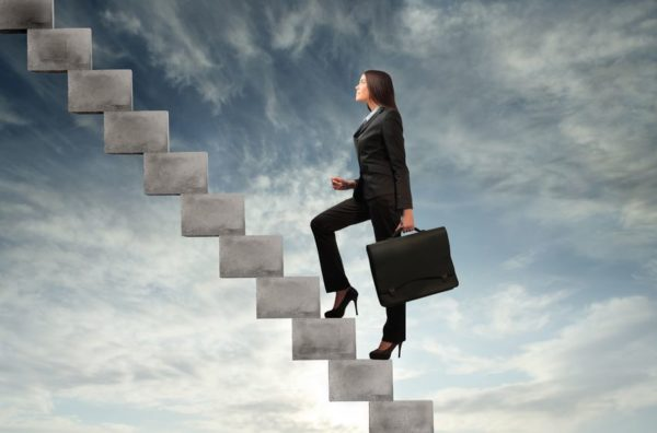 businesswoman stepping up a staircase with sky in the background