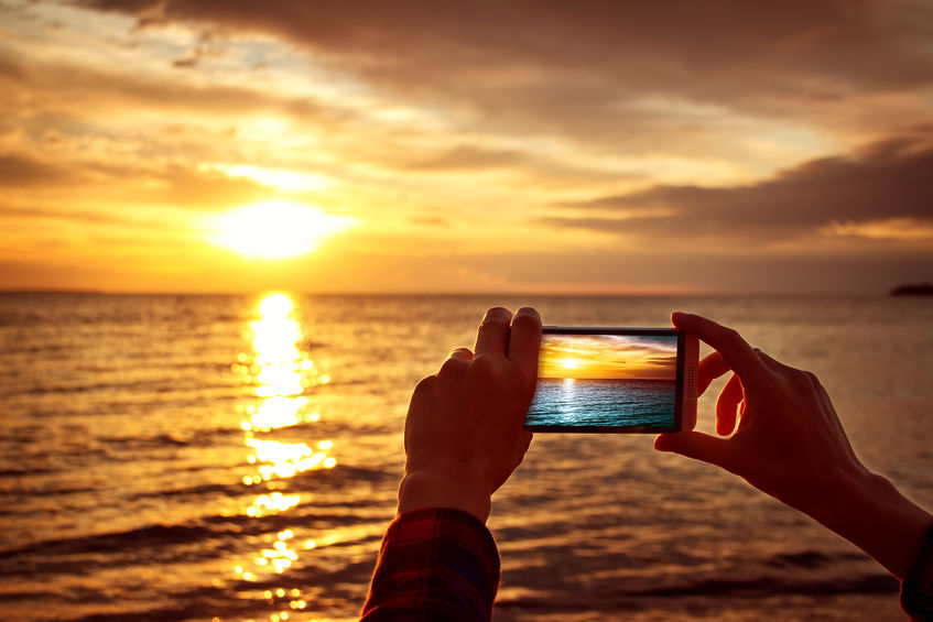 photo of phone taking picture of spectacular sunset